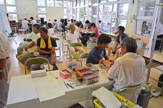 島内の各会場でスタートした特定検診を受診する市民=24日午後、おもと農村多目的集会施設