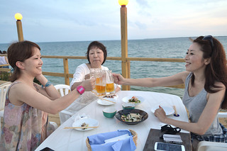 心地よい海風に当たりながらビールを楽しむ観光客ら=26日夕、ホテルサンシャイン