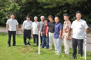 2011年6月に続きヒカンザクラを植樹した名護市議「礎の会」のメンバーと箕底用一石垣市議ら(左)=26日午後、林業総合センター広場