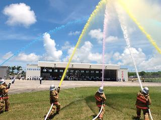 石垣市消防本部の移転式典終了後、庁舎第2車庫前で行われた一斉着色放水=1日正午ごろ