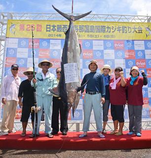 109㌔のシロカワカジキを釣り上げ、ポーズを取る前西原好弘さん(カジキの左)=6日午後、久部良漁港カジキ釣り会場(大会事務局提供)