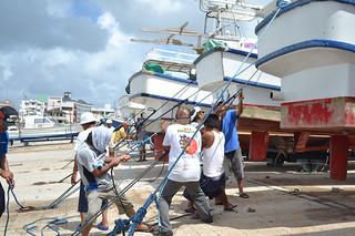 台風接近を前に陸揚げした船をロープで固定する漁業関係者ら=7日午前、登野城漁港