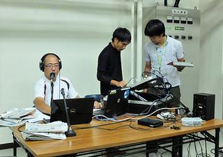 バンナ岳頂上にある沖縄県石垣テレビ中継局に機材を持ち込み、生放送を行うFMいしがきのスタッフら=8日午前11時50分ごろ