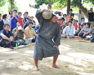 川平の豊年祭で勇ましくビッチュル石を奉納する担ぎ手=10日午後、赤イロ目宮鳥御嶽
