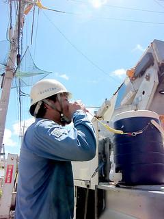 照りつける強い日差しの下、一息入れ、水分を補給する作業員=14日午前、市道慶田山線
