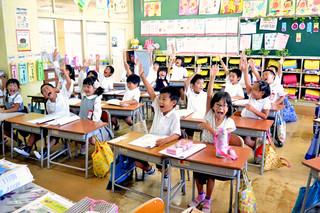 「夏休み楽しみにしている人?」の問いかけに「ハーイ!」と元気よく答える石垣小学校1年1組の児童たち=18日午前、同校