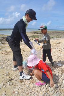 大浜海岸の清掃に汗を流す参加者=20日午前