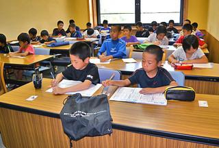 夏休み特別教室が始まり、学習に取り組む児童たち=29日午前、市立図書館洋会議室