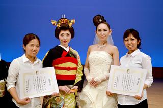 県美容技術選手権大会で高い技術力が認められ、全国大会出場を獲得した新城桃子さん(左端)と翁長友美さん(右端)=29日午後、浦添市てだこホール