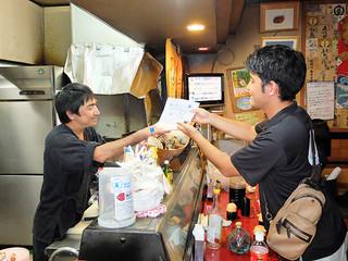 石垣市水産課の職員から注意喚起のチラシを受け取る居酒屋の店主(左)=7月25日夕、美崎町内