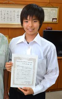 「高校生のための素粒子サイエンスキャンプ」の「博士号認定証」と書かれた修了証を手にする八重山高校2年の上西凜太郎君(17)=14日午後、同校校長室