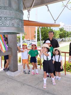 「終戦の日」平和祈念鐘打式で、世界平和の鐘を打ち鳴らす子どもたち=15日正午すぎ、新栄公園内