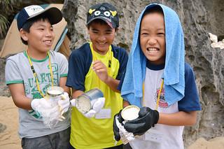 缶詰の空き缶を飯ごう代わりにし、炊きたてのご飯に笑顔をみせる子どもたち=16日午後、山原川河口