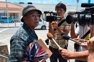 定例会終了後、取材に応じる慶田盛安三教育長=18日午後、県労働金庫八重山支店前
