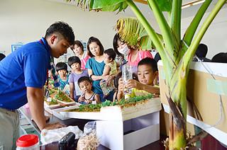 模型を使った赤土拡散や対策効果の検証実験コーナーは人気を集めた=23日午後、大浜公民館