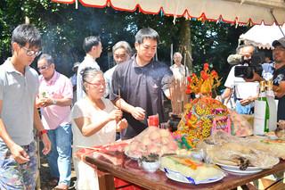 土地公祭で、土地公に線香をささげる人たち=7日午前、名蔵御嶽