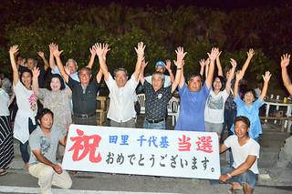 トップ当選を果たし、万歳三唱で喜ぶ田里千代基氏の支持者ら =7日夜、祖納地区の選対事務所