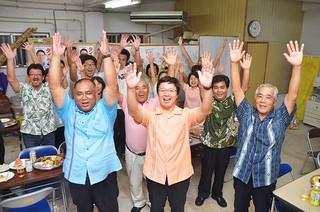 トップ当選を果たし、万歳をして喜ぶ平良秀之氏(中央)と支持者たち=8日午前1時45分ごろ
