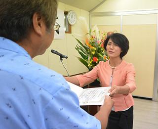 竹富町議会初めての女性町議として当選証書を受け取る三盛克美氏=10日午前、町役場委員会室