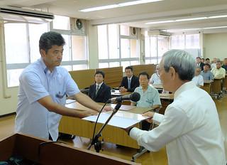 当選証書を受ける友寄永三氏(左)ら=11日午前、市役所2階会議室