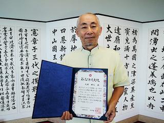 美ら島沖縄大使に認証された大塚勝久さん=17日午後、県庁(大塚さん提供)