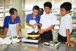八重山農林高校の体験入学。調理を指導する高校生(中央左)とアドバイスを受ける中学生=22日午後、同校