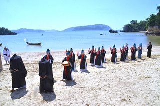 全身黒ずくめのアンガー行列が厳かに入場した西表島の節祭=26日午後、前泊海岸