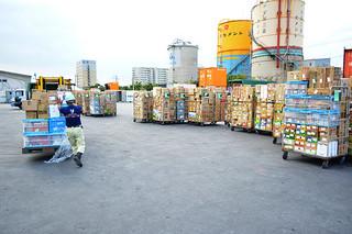 台風19号の影響で5日ぶりに本島から届いた生活物資をコンテナから下ろす作業員ら=15日夕、石垣港