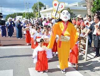 宮良村結願祭のジョウリキィ(道行列)で子や孫を伴ったミルクが練り歩き、歩道は見物客で埋め尽くされた=26日午後、宮良村排所(オーセー)付近