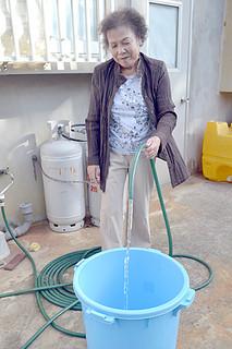 購入したばかりのプラスチックのバケツに水をためる松竹サエ子さん=30日午後、小浜島