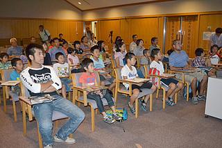 インターネットを通じて、西原町で開かれた「若田光一宇宙飛行士のミッション報告会」に参加した市民=2日午後、石垣市立図書館