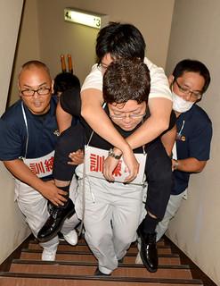 津波避難訓練で傷病者を担架で指定避難ビルに運ぶ参加者ら=5日午前、南の美ら花ホテルミヤヒラ