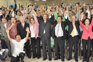 支持者とともにバンザイ三唱で初当選を喜ぶ翁長雄志氏=16日夜、那覇市壷川の選対総本部