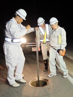 夜間断水で仕切り弁を閉める作業員ら=20日午後11時、石垣市健康福祉センター近く