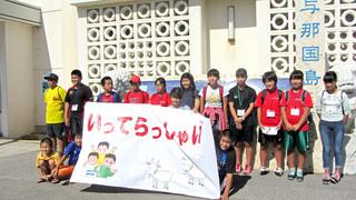 下級生に見送られ、台湾へ出発する与那国町の小学6年生たち(後列の11人)=24日、与那国空港