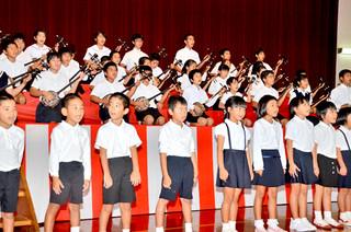 波照間小創立120周年と同中66周年記念式典で「波照間節」を斉唱する児童生徒ら=23日午後、同校体育館