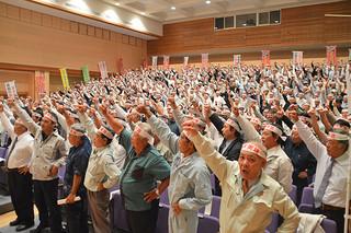 さとうきび生産確立県農業代表者大会でガンバロー三唱で気勢を上げる生産農家ら=25日午後、南風原町立中央公民館