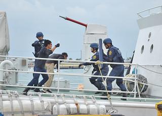 訓練で刃物を持った犯人役の男を取り囲む石垣海上保安部の職員ら=26日午後、石垣港浜崎地区国際埠頭