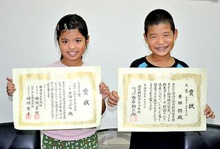 作文コンクールで兄妹そろって入賞した平田つぶらさん(左)と誇君=26日夕、平真小校長室