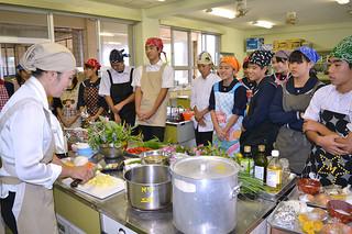 嵩西洋子さん(左)から島のスパイスカレーの作り方を教わる生徒たち=12日午前、石垣第二中家庭科教室