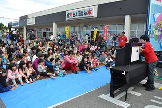 「本とあそぼう全国訪問おはなし隊」が石垣島を訪問。紙芝居を楽しむ親子たち=14日午前、ブックスきょうはんやいま店前
