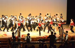 一糸乱れぬ動きで「Camaraderie ~この地球(ほし)に音楽を~」を披露する部員ら=25日夜、市民会館大ホール