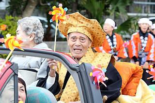 97歳のカジマヤーを迎え、パレードで祝福を受ける山城清有さん=2日午前、平得公民館近く
