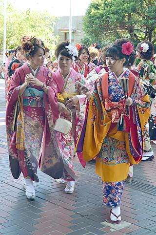 石垣市の成人式で、振り袖や琉装など華やかな衣装に身を包み、写真に収まる新成人たち=4日午後、市民会館ピロティ
