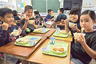 島野菜の七草雑炊を味わった児童ら=7日午後、登野城小