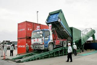 初荷の粗糖を砂糖運搬船「栄球丸」に積み込む大型トラック=19日午前、石垣港
