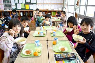 初めて提供された汁そばをほおばる真喜良小学校3年2組の児童たち=27日午後、同校