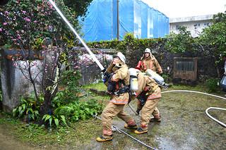 文化財防火デーにちなみ、消火訓練を行う市消防の消防隊員=27日午後、旧宮良殿内