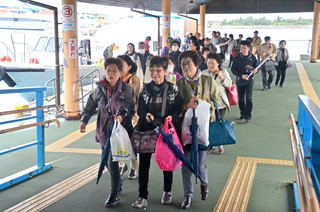 竹富町内の離島巡りを終えて石垣港に着いた観光客ら。竹富町は滞在型観光推進に向けて民宿泊支援システムを整備していく=1月21日午後
