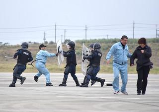 訓練で人質役の女性(右)を救出し、ハイジャック犯役の男性を取り押さえる警察官ら=30日午後、南ぬ島石垣空港